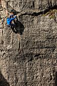 Man wearing blue jacket, grey helmet and various climbing gear climbing Corbet's Couloir, Jackson Hole, Wyoming.