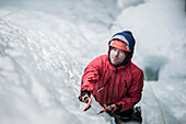 Man with red jacket and orange helmet and ice axes lead climbing an ice fall in Simplon Pass shooted from above. Valais, Switzerland.