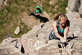 Beautiful italian blonde girl climbs a 6b crack route in Balmanolesca, the most historical granite crag in Ossola, on a sunny spring day. Varzo, Italy.