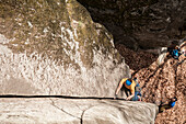 Man trad climbing a crack in Cadarese, one of the main places in Europe for trad and crack climbing. Premia, Ossola, Italy.