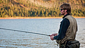 A young man in his early thirties  fly fishing near Durango, Colorado.