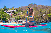 Girl travels by sup surfboards at coastline of Nusa Lembongan and Nusa Ceningan islands. Indonesia.