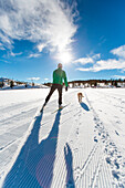 Man cross country skiing with dog.