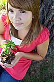 Thirteen Year Old Girl Seated Beside Tree Holding Small Tree, Winnipeg, Canada