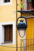 'An ornate lamp hanging from a building; Barcelona, Spain'