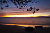 'Sunset over the ocean horizon and rocks on the sandy shore; Island of Hawaii, Hawaii, United States of America'
