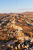 'Hot air balloons in flight over a rugged landscape; Cappadocia, Turkey'