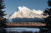 'Snow covered mountain framed by silhouetted evergreen trees with snow covered lake and blue sky; Banff, Alberta, Canada'