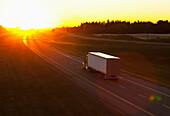 'Truck heading down a highway at sunset; Edmonton, Alberta, Canada'