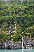 'Waterfalls spilling down a green forested mountain side over a cliff into Passage cannal, Prince William Sound; Whittier, Alaska, United States of America'