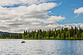 'A couple and young girl in a red canoe on Byers lake with green forested shoreline, Byers Lake Campground, Denali State Park; Alaska, United States of America'