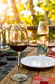 'Glasses of red wine on a table set for a meal; Ontario, Canada'