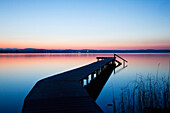'A wooden dock leading out to a tranquil lake at sunset; Starnberger See, Bavaria, Germany'