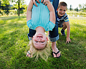 'Mother hanging her daughter upside down in a park; Edmonton, Alberta, Canada'
