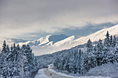 Clouds clearing over Seward Highway from the Kenai Mountains above Turnagain Pass after a winter snow storm, fresh snow in the trees, early morning sun, Turnagain Pass, Chugach National Forest, Southcentral Alaska, USA.