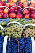 'Baskets of purple and green grapes and ripe necatarines at a farmers market; Toronto, Ontario, Canada'