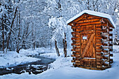 'Log outhouse by a meandering creek in snow, Chena Hot Springs Resort; Fairbanks, Alaska, United States of America'