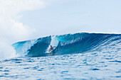 'Surfer riding perfect waves in the South Pacific, Tahiti, French Polynesia'