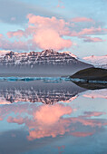 Panoramic view across the calm water of Jokulsarlon glacial lagoon towards snow-capped mountains and icebergs bathed in the last light of a winter's afternoon, at the head of the Breidamerkurjokull Glacier on the edge of the Vatnajokull National Park, Sou