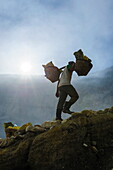 Backlit image of workers loaded with sulphur pieces cut out from a sulphur mine on Ijen crater lake, Java, Indonesia, Southeast Asia, Asia