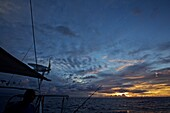 Impressive clouds at sunrise seen from a sailing boat, yacht with wind generator, Atlantic ocean, Sailing