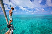 Yachtsman standing on the bow of a sailing boat, yacht in the Caribbean sea