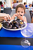 Girl eating mussels, Palavas-les-Flots, Montpellier, Herault, Languedoc-Roussillon, France