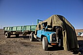 Truck driver repairing the engine of his truck under a cover due to cold weather  Mongolia