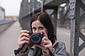 Young woman taking photos on Hacker Bridge, Munich, Bavaria, Germany
