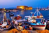 Cretan boat moored Heraklion harbour and Venetian fortress Koules Castle, Iraklio, Crete, Greece.