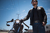 Low angled portrait of male hipster motorcyclist
