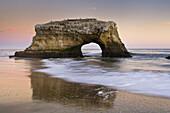 Arch rock and waves on sand beach in evening light, Santa Cruz, California.