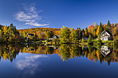 Cottages and fall foliage color in the trees reflected in a calm lake at La Beauport, Quebec, Canada.