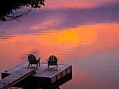adirondack chairs lakeside on dock