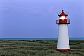 Lighthouse List West with light on in the dunes, with beach and North Sea, Sylt, North Frisian Islands, Schleswig-Holstein, Germany, Europe.