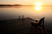 sunrise over a lake with a chair on a dock in the foreground