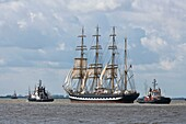 Russian tall ship Kruzenstern and two towboats on the river Weser in Bremerhaven, Germany, Europe