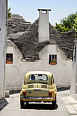 Fiat 500 and trulli houses at Alberobello, Puglia, Italy.