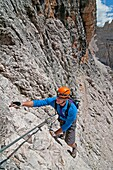 Man climbing the Giovanni Lipella via ferrata on Tofana De Rozes in the Dolomite Mountains near the city of Cortina in northern Italy