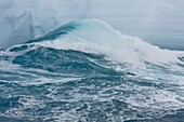 Waves break against the base of a huge tabular iceberg, melting the ice along a band near the Antarctic Peninsula during the summer months   Eventually this berg will become top heavy and flip  More icebergs are being created as global warming is causing