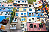 Hundertwasserhaus (1985) is an apartment house built in the style following the Moldiness Manifesto attributed the Austrian artist Friedensreich Hundertwasser. This expressionist Viennese landmark includes a forested roof terrace, rainbow hues, undulating