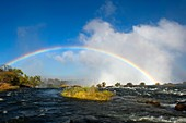 Rainbow over Victoria Falls seen from the shore of the Zambezi River at the section above the falls near Livingston in Zambia.