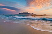 Wide angle landscape photo of a wave washing over a beach in sunset light with table mountain in the background. Bloubergstrand, Cape Town, South Africa.
