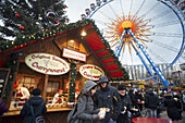 Ferris wheel and currywurst at the Christmas market in front of the Neptunbrunnen fountain, Alexanderplatz, Berlin. Snack Bar at Alexanderplatz. Bells, tinsel, carols, decorated trees? Christmas has definitely arrived. This special moment of the year star