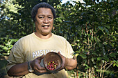 Atiu Island. Cook Island. Polynesia. South Pacific Ocean. One of the growers teaches coffee beans grown on the island of Polynesia. Atiu has a long history of growing coffee. Missionaries established it commercially in the early 19th century. By 1865, ann