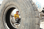 Worker behind a tire, tire repair shop, Ulaanbaatar, Mongolia