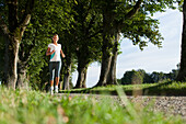 Young woman jogging, alley near Aufkirchen, Berg, Bavaria, Germany