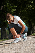 Female jogger doing up the shoelaces, alley near Aufkirchen, Berg, Bavaria, Germany
