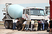 Workers pushing broken transit-truck mixer, Ulaanbaatar, Mongolia