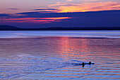 Two persons swimming in lake Chiemsee, Chieming, Bavaria, Germany